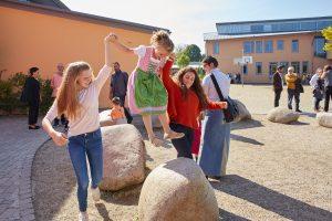 Schülerin springt mit Hilfe der Paten von Stein zu Stein.