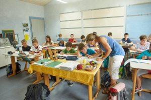 Klassenlehrerin unterstützt einen Schüler